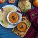 tomato chutney in a wooden bowl and in a ceramic bowl served with dosa