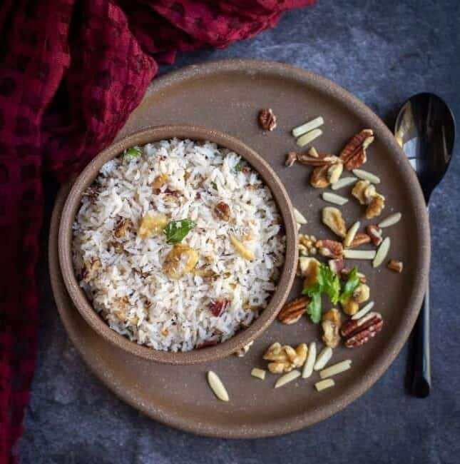 square image of coconut rice in a ceramic bowl with nuts on the side