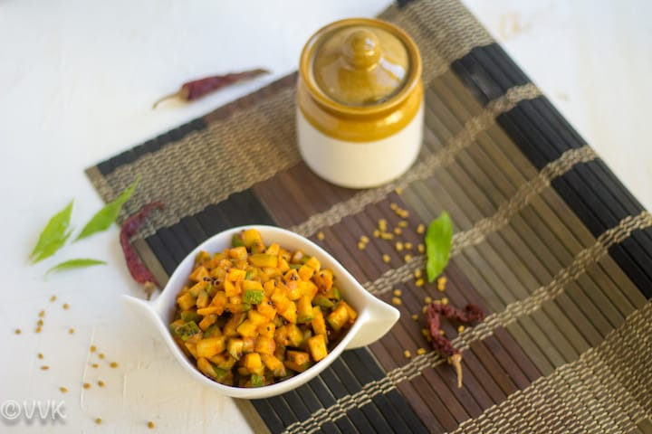 cut mango pickle in a white bowl with few curry leaves and red chilies on the side
