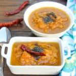 Mango Pachadi or Mambazha Pachadi served in two white bowls with two chilis in the background