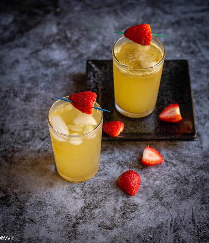 sprite jaljeera refresher  topped with strawberry served in two glasses with strawberry pieces on the side