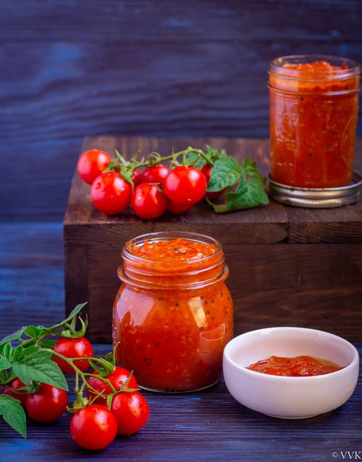 homemade tomato pickle placed in a two mason jars with tomatoes on the side as a decor