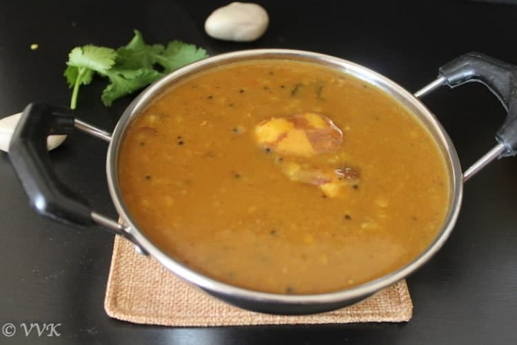 Palakottai Kuzhambu or Jackfruit Seed Sambhar ready and served in a metal bowl with a few sprigs of cilantro in the back