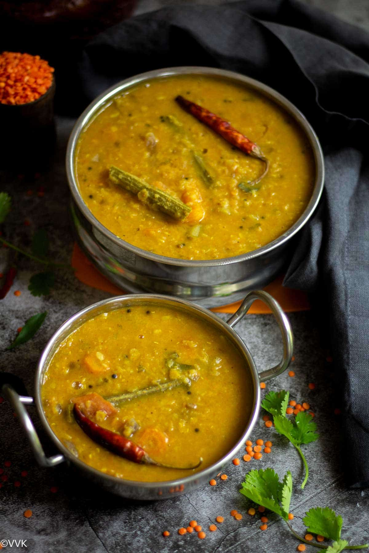 pressure cooker sambar served in stain less steel containers with masoor dal on the side