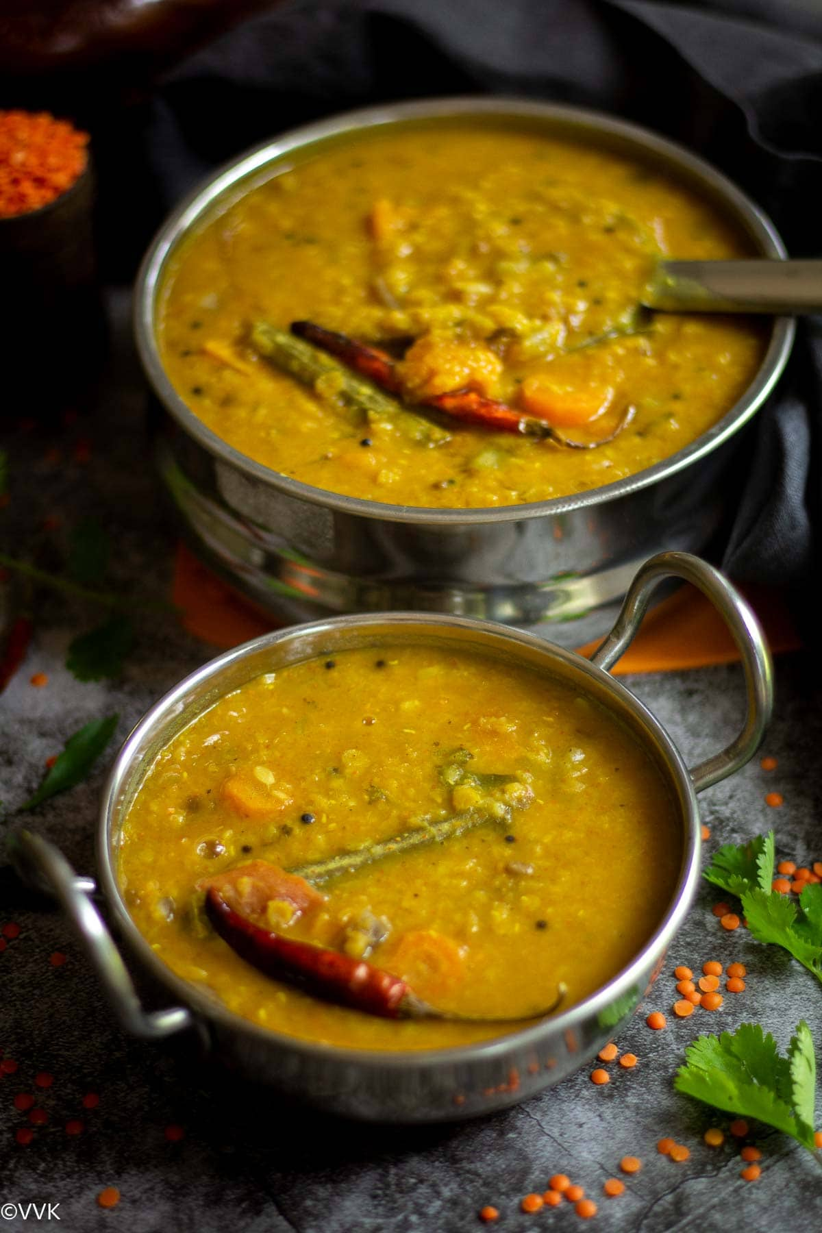 masoor dal sambar served in kadai vessel with cilantro on the side and with some masoor dal sprinkled