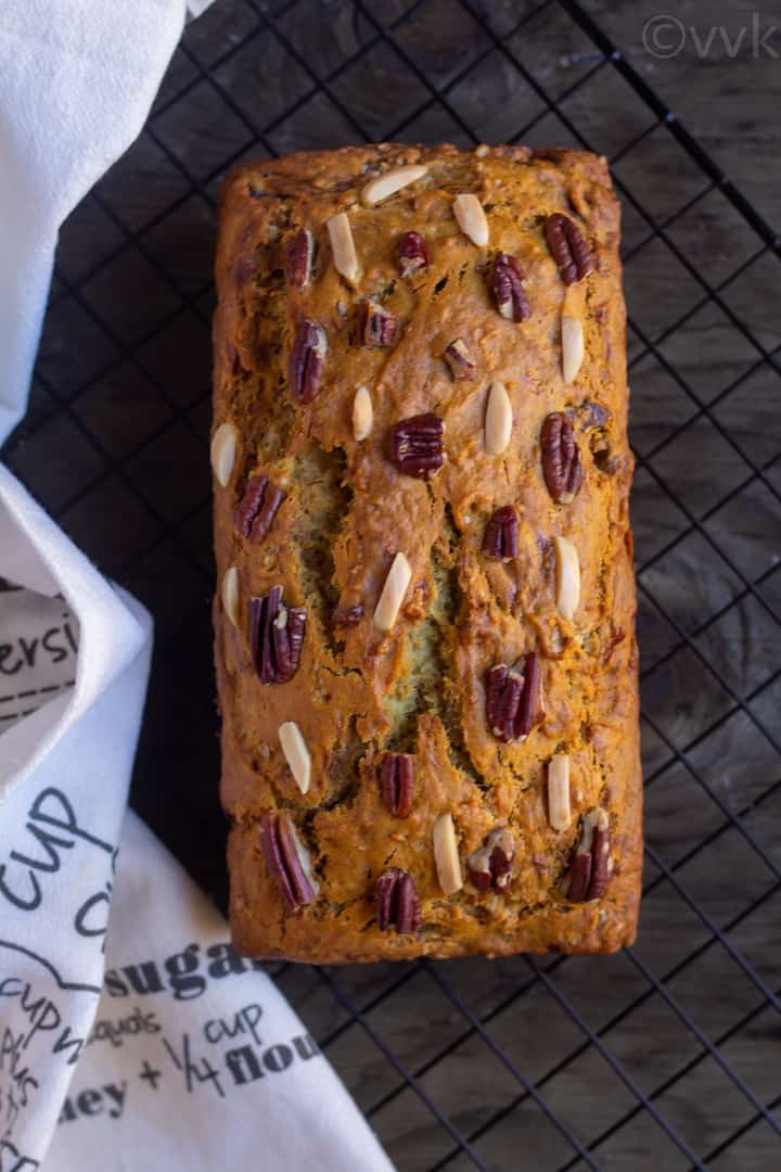 vegan banana bread place on a cooling wire rack with a white fabric on the side