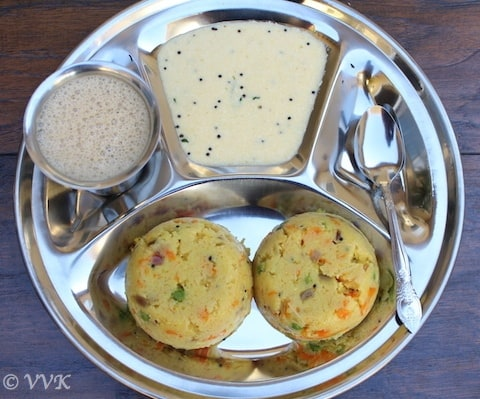 A big metal tray with Rava Kichadi served with coconut chutney and a metal spoon on the right side