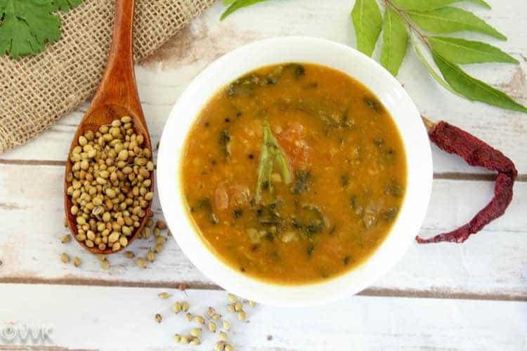 Overhead on the delicious Vendiya Keerai Kuzhambu or Methi leaves Sambar served in a white bowl