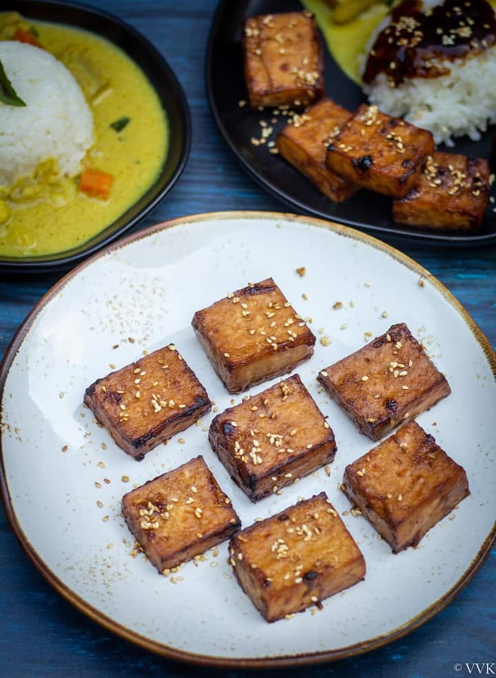teriyaki tofu in a white plate with curry and rice on the top