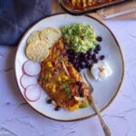 square image of enchiladas served with guac, beans and sour cream