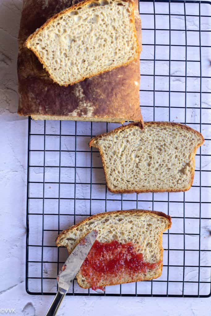 overhead shot of wheat bread loaf with slices on the cooling rack. One slice with jam applied