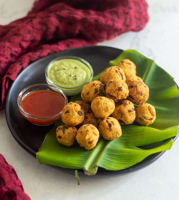 tea kadai style pakoda placed on a banana leaf on a black plate with condiments on the side