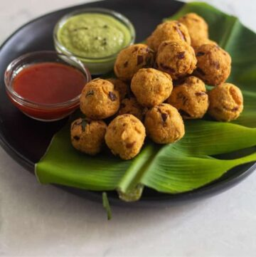medhu pakoda placed on banana leaf on a black plate with condiments on the side