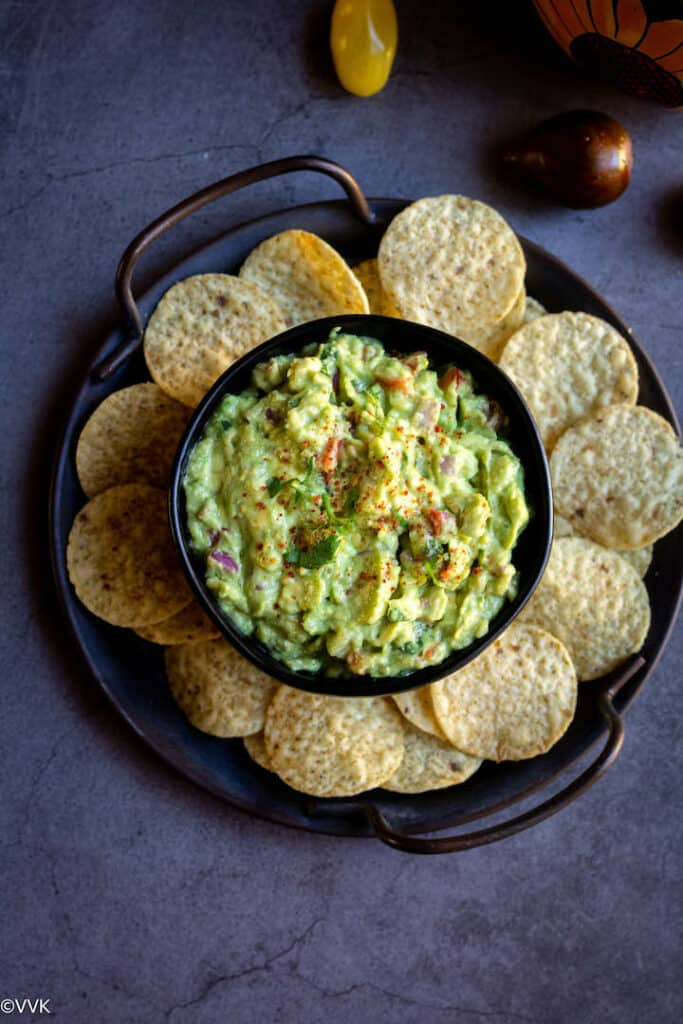 easy homemade guacamole served in black bowl with chips and with some tomatoes on the side