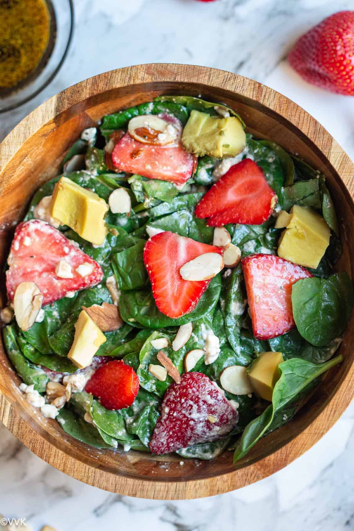 close up shot of spinach strawberry salad with nuts in a wooden bowl