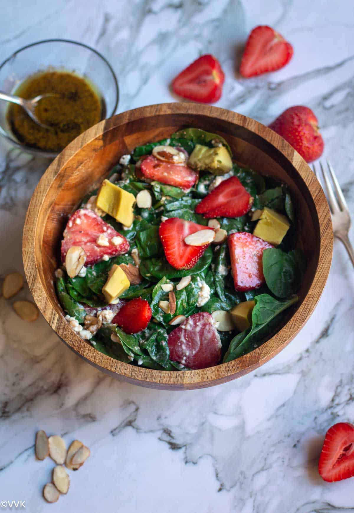 spinach salad with strawberries and almonds served in wooden bowl