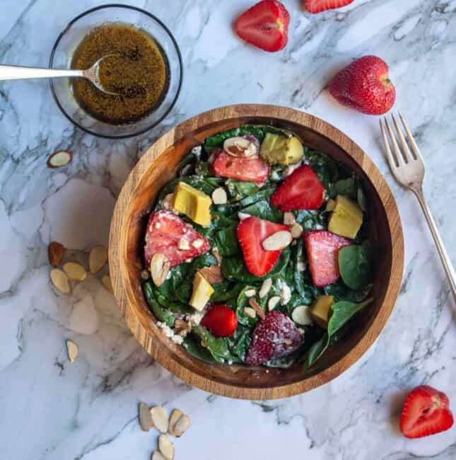 square image of spinach and strawberry salad in a wooden bowl with the dressing on the side
