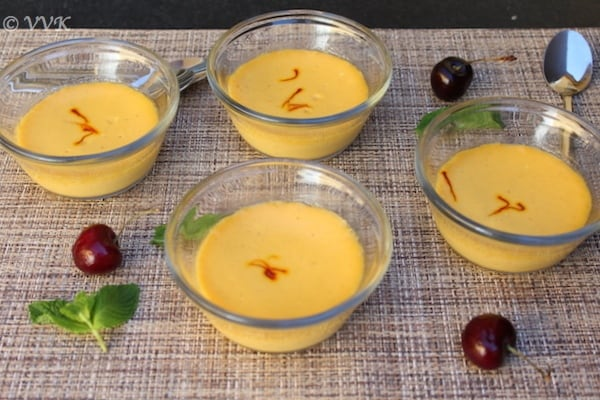 Mango yogurt dessert with cherries lying around