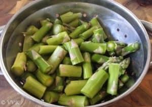 Asparagus chopped into small pieces inside a metal bowl