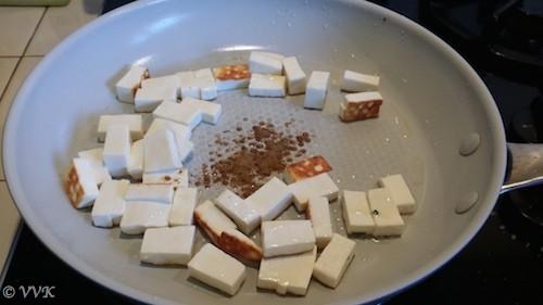 Adding cumin powder to the paneer