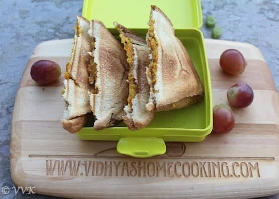 Vegetable Sandwich served in a lunch box with grapes around the box on a wooden board