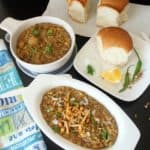 Healthy Missal Pav served in two types of white bowl with bread, lemon and chilis on the side