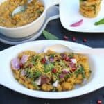 Ragda Pattice or Ragda Patties served in white bowls on a dark surface decorated with pomegranate seeds