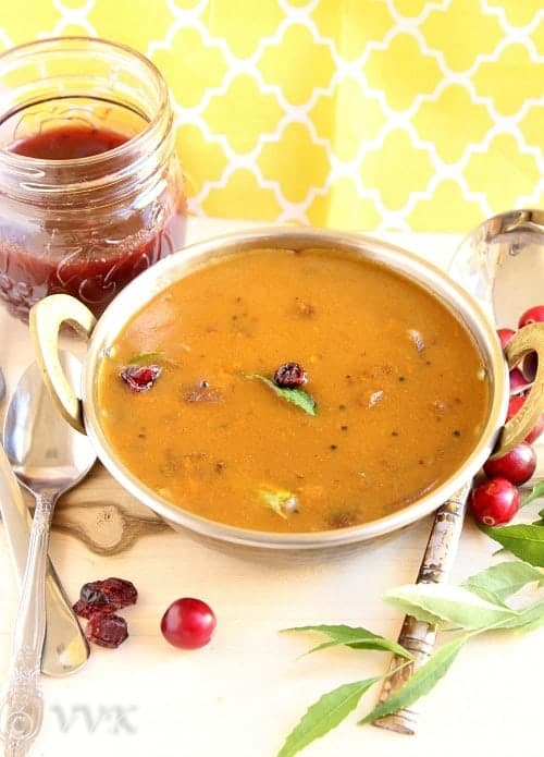 Cranberry Sauce Vathal Kuzhambu or Gravy served in a metal plate with metal spoons and fork next to it and cranberries on a wooden table