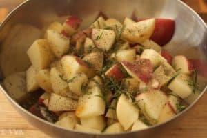 Adding rosemary and spices to the potatoes