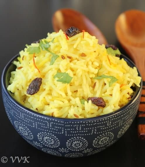 Vegan Turmeric Saffron Rice generously served in a dark bowl with two wooden spoons in the back
