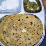 Mooli Paratha or Radish Paratha served in a metal lunch box with a couple of sides