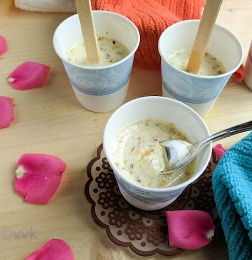 Almond Kulfi in three paper cups with rose petals around