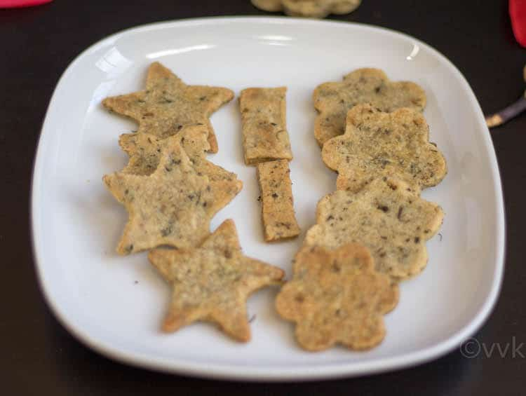 Baked Methi Mathri cookies of various shapes presented on a big white plate