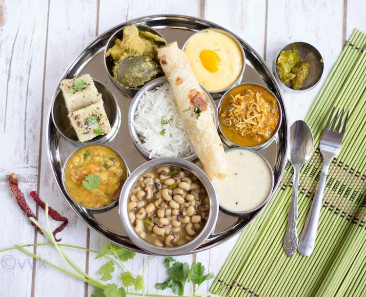 Gujarati Thali served on a tray with a circle shape with a spoon and fork on the side