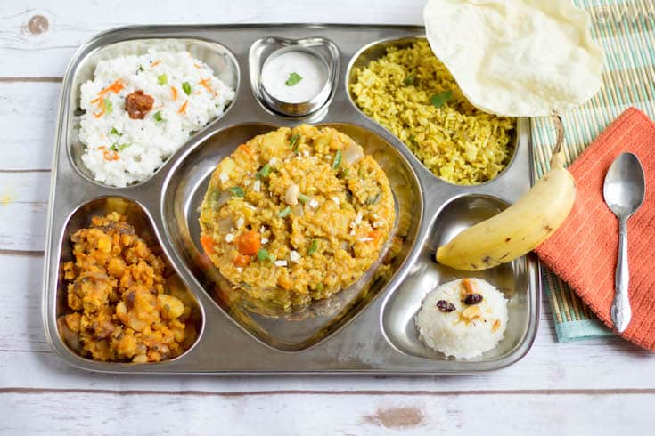 Saravana Bhavan Style Executive Thali with each dish titled on a wooden surface with a spoon next to the tray