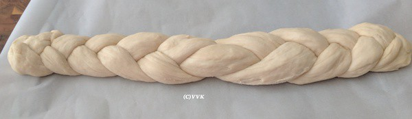 Placing the braided bread on a baking tray lined with parchment paper