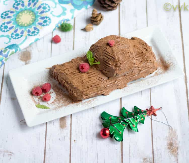 Christmas Special Eggless Yule Log Cake served with raspebrries and cute little Christmas trees