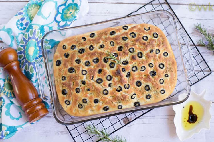 Focaccia Bread with Olives and Rosemary in a glass tray on a white wooden table