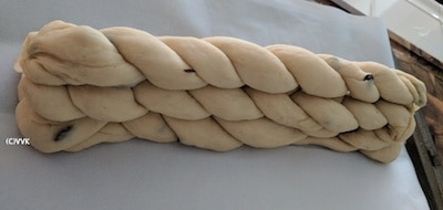 Lining a baking tray with parchment paper and placing the four strand braid first