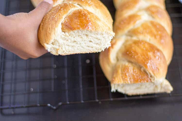 Holding one Braided Eggless Challah Bread in the right hand with another one blurred in the background
