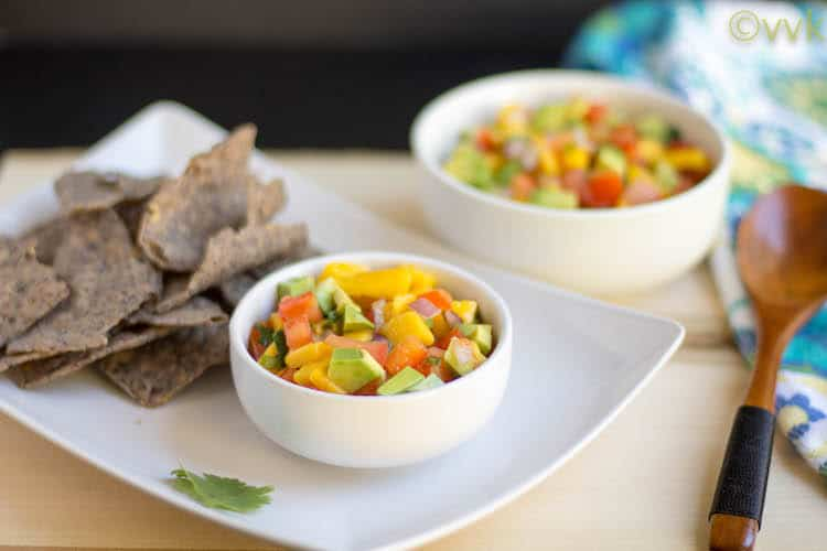 Mango Avocado Salsa Served with Chips on the Side and a Wooden Spoon Next to It
