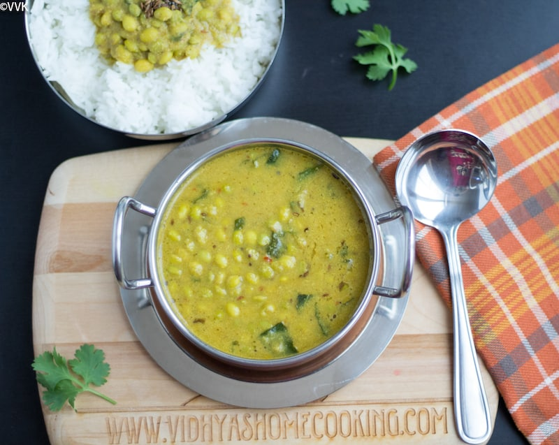 Instant Pot Avarekalu Huli Saaru, Hyacinth Beans Curry, with a bowl of rice and cilantro on a dark surface