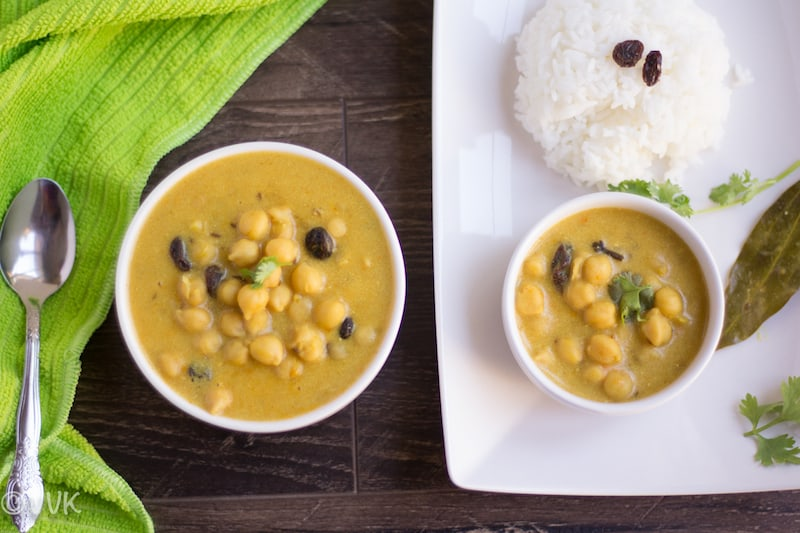 Instant Pot Channa Madra - Pahari Cuisine Special Channa Madra Another Great Overhead on the Dish with a Spoon on the Green Fabrics and Another Portion Served in a White Plate and Some Rice Next to It