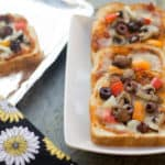 Vegetable Bread Pizza served in white plates on a greyish surface