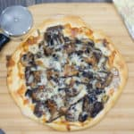 Wild Mushroom Pizza ready to be cut into slices on a wooden board