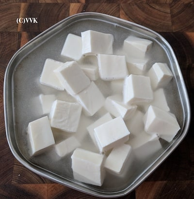 Cutting paneer into small cubes and soaking in hot water