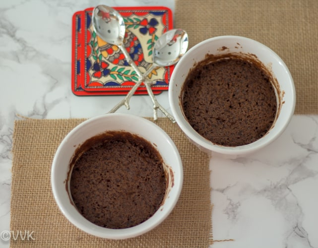 Eggless Microwave Chocolate Cake serve in two cute ramekins with two spoons next to them
