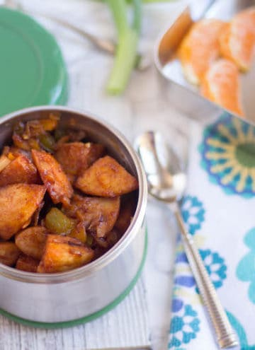 Idli Manchurian served in a cute little box with fruits blurred in the background