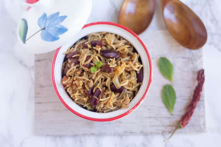 Rajma Pulao - Instant Pot Rajma Pulav - Served and Ready on the Table with Two Wooden Spoons, Chili Pepper and Two Mint Leaves