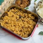 Tamarind Rice or Puliodarai served in a lunchbox with more sides next to it